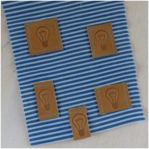 Lederlabel in verschiedenen Formen auf einem Stück Stoff zur Veranschaulichung genäht