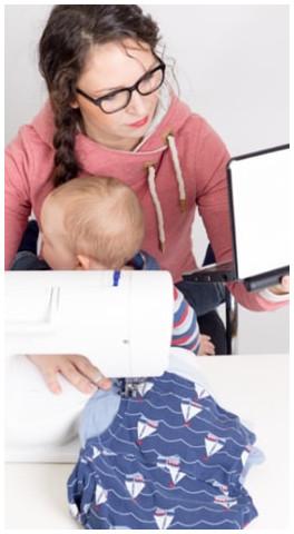 Yvonne vor der Nähmaschine mit Kind auf dem Schoß und Laptop in der Hand
